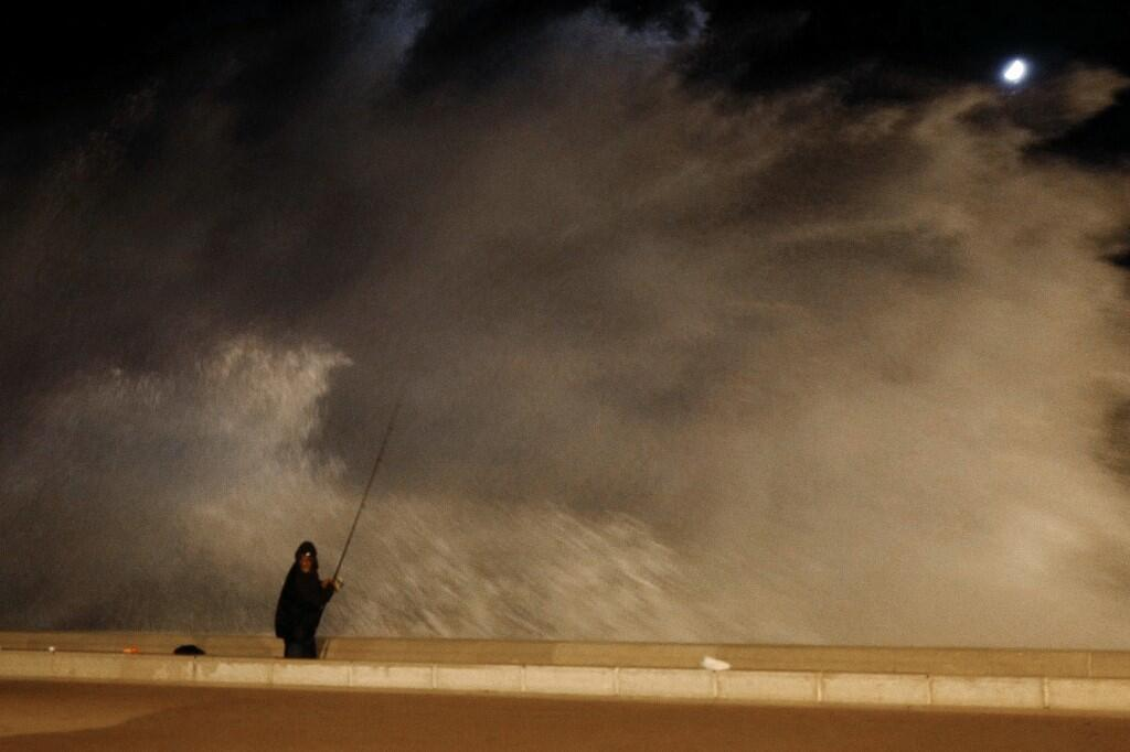 A fisherman is surprised by a big wave on the French city of Nice, 3 November 2019. Storm winds blasted southern France, whipping up giant ocean waves, uprooting trees and leaving some 140,000 people without electricity.