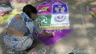 A woman makes a rangoli during a rangoli making contest to mark International Women's Day in India