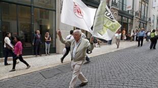 Homem caminha com duas bandeiras do Partido Socialista durarnte campanha para eleições municipais em Lisboa.