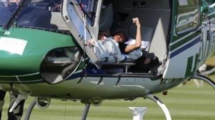 Neymar, deitado na maca, acena para a imprensa em sua despedida da seleção.