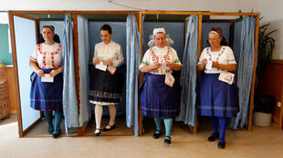 Hungarian women wearing traditional costumes attend a referendum on EU migrant quotas.