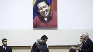 Raúl Castro e Nicolás Maduro se abraçam sob foto de Chávez, em Havana, 27 de abril