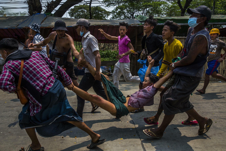 Le 14 mars 2021, des gens portent un homme avec une blessure par balle. Une photo du lauréat du prix Visa d'or News 2021 sur la révolution du printemps en Birmanie.  © Lauréat du Visa d'or News