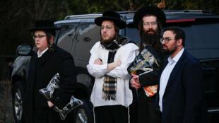 Des membres de la communauté juive se rassemblent devant le domicile du rabbin Chaim Rottenbergin Monsey, à New York, le 29 décembre 2019, après une attaque à la machette qui a eu lieu plus tôt devant le domicile du rabbin.