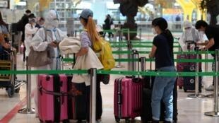Tres pasajeras, una de ellas con traje protector completo, esperan a acceder a una zona de embarque del aeropuerto de Barajas, el 20 de junio de 2020 en Madrid