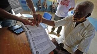 Un électeur utilise son empreinte digitale pour voter dans un bureau de vote d'Igarape Miri, dans l'Etat brésilien de Para, lors des municipales du 15 novembre 2020.