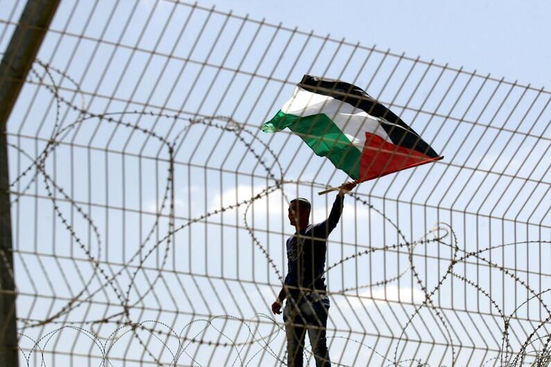 一名巴勒斯坦人挥舞旗帜
