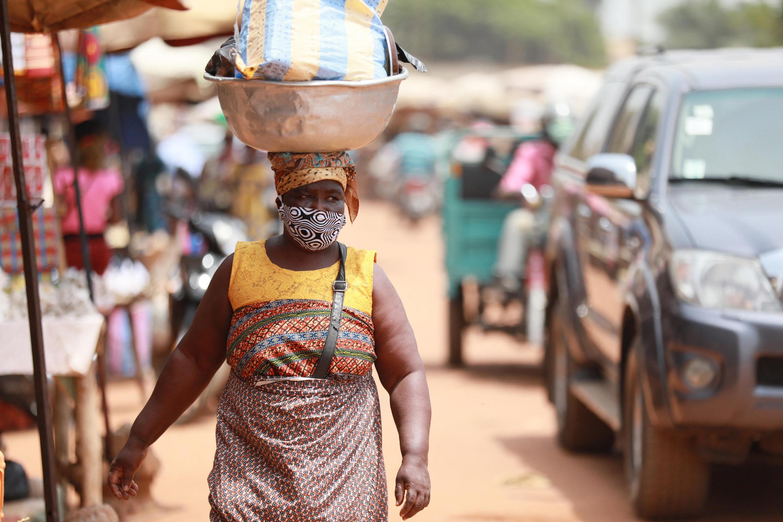 IMAGE Une femme marche dans les rue de Lomé au Togo avec un masque, mesure barrière contre le coronavirus.