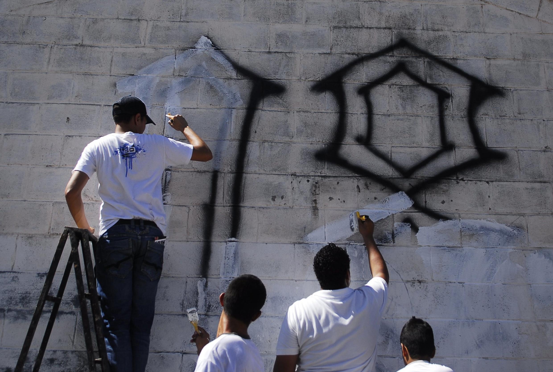 Pandilleros borrando sus graffitis, en San Salvador, el 4 de enero de 2013.