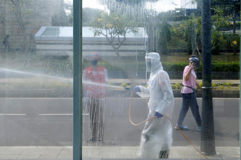 Le personnel de la Croix-Rouge désinfecte par pulvérisation pour prévenir la propagation du coronavirus à Jakarta en Indonésie, le 31 mai 2020.