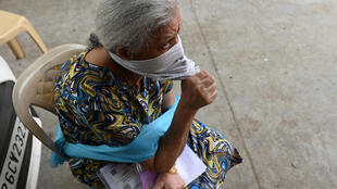 A woman waits for her turn to receive a Covaxin Covid-19 vaccine at a health centre in New Delhi