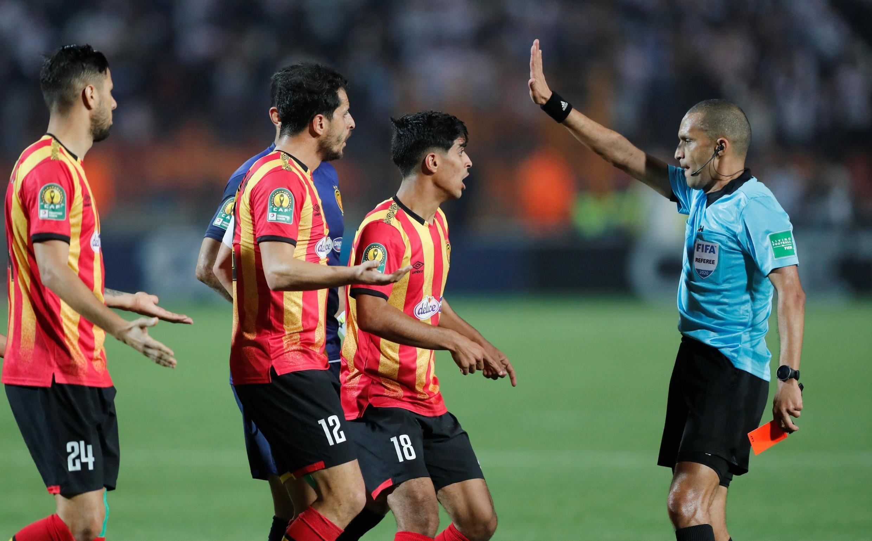 Les joueurs de l'Espérance Tunis et l'arbitre Rédouane Jiyed, lors du quart de finale aller de la Ligue des champions africaine face à Zamalek.