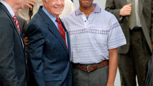 Former US President Jimmy Carter poses with Aijalon Mahli Gomes, an American citizen who was detained in North Korea.