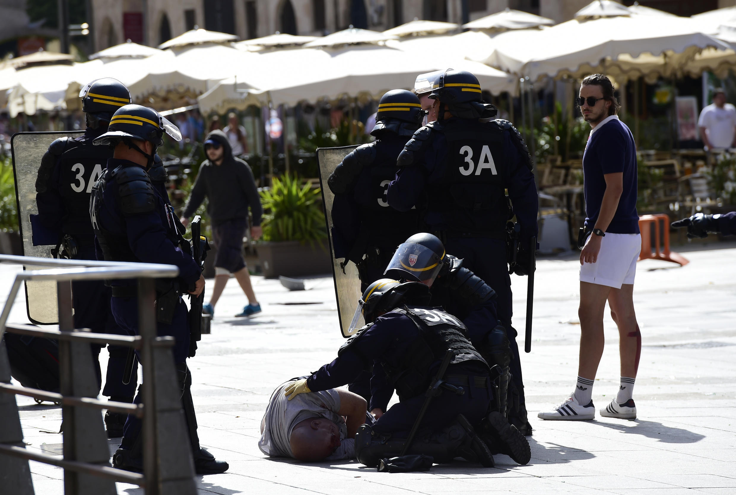 Police attend to injured England fan Andrew Bache following clashes with Russian fans in Marseille ahead of the Euro 2016 football match between England and Russia