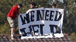 Взбунтовавшиеся мигранты устанавливают на крыше одного из зданий центра в Виллавуде плакат с призывом о помощи 21/04/2011