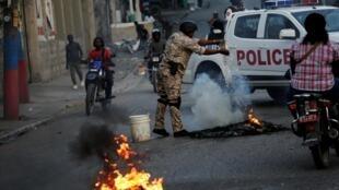 Un policier verse de l'eau sur des pneus enflammés lors de manifestations à Port-au-Prince, le 19 février 2020.