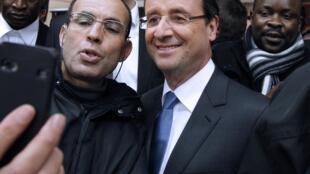 O candidato socialista François Hollande posa para foto em um centro comercial na cidade de Ivry.