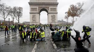 Des manifestants portant des gilets jaunes face à la police anti-émeute française, lors d'affrontements sur la place de l'Etoile près de l'Arc de Triomphe à Paris, le 1er décembre 2018.