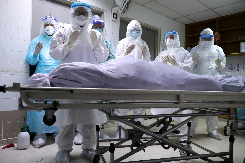 Los miembros de la familia de una víctima del coronavirus rezan en la morgue de Kuala Lumpur.