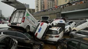 Habitantes contemplan la pila de vehículos que han arrastrado las lluvias torrenciales en Zhengzhou, centro de China, el 22 de julio de 2021