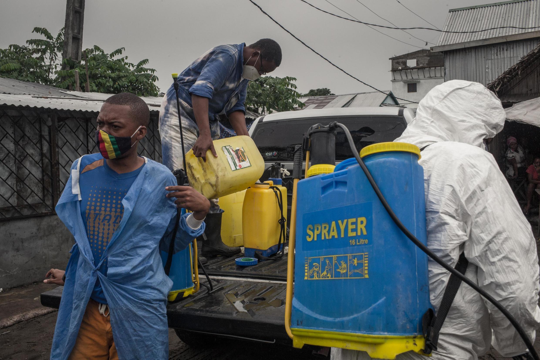 Des fonctionnaires du ministère de la Santé déchargent des pulvérisateurs d'une camionnette pour désinfecter dans le quartier de Tsarakofafa, à Tamatave, grande ville portuaire de Madagascar, Plus gros foyer d'épidémie de coronavirus, le 4 juin 2020.