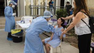 Una colegiala chipriota se somete a una prueba de hisopado para el coronavirus en su primer día de regreso a la escuela en la capital, Nicosia, tras el levantamiento de un cierre de dos meses.