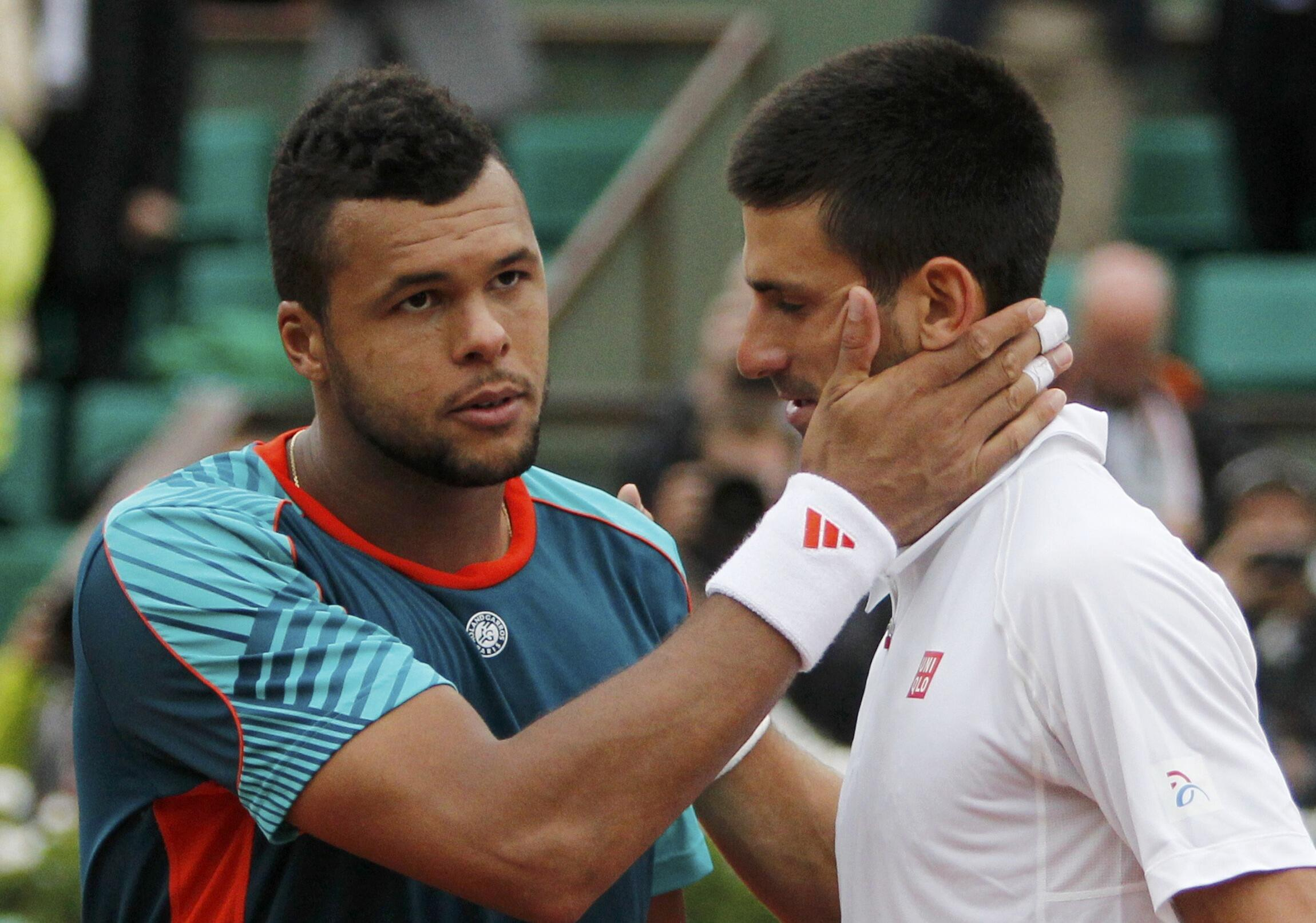 Novak Djokovic of Serbia shakes hands with Jo-Wilfried Tsonga of France after winning his quarter-final match, 5 June, 2012