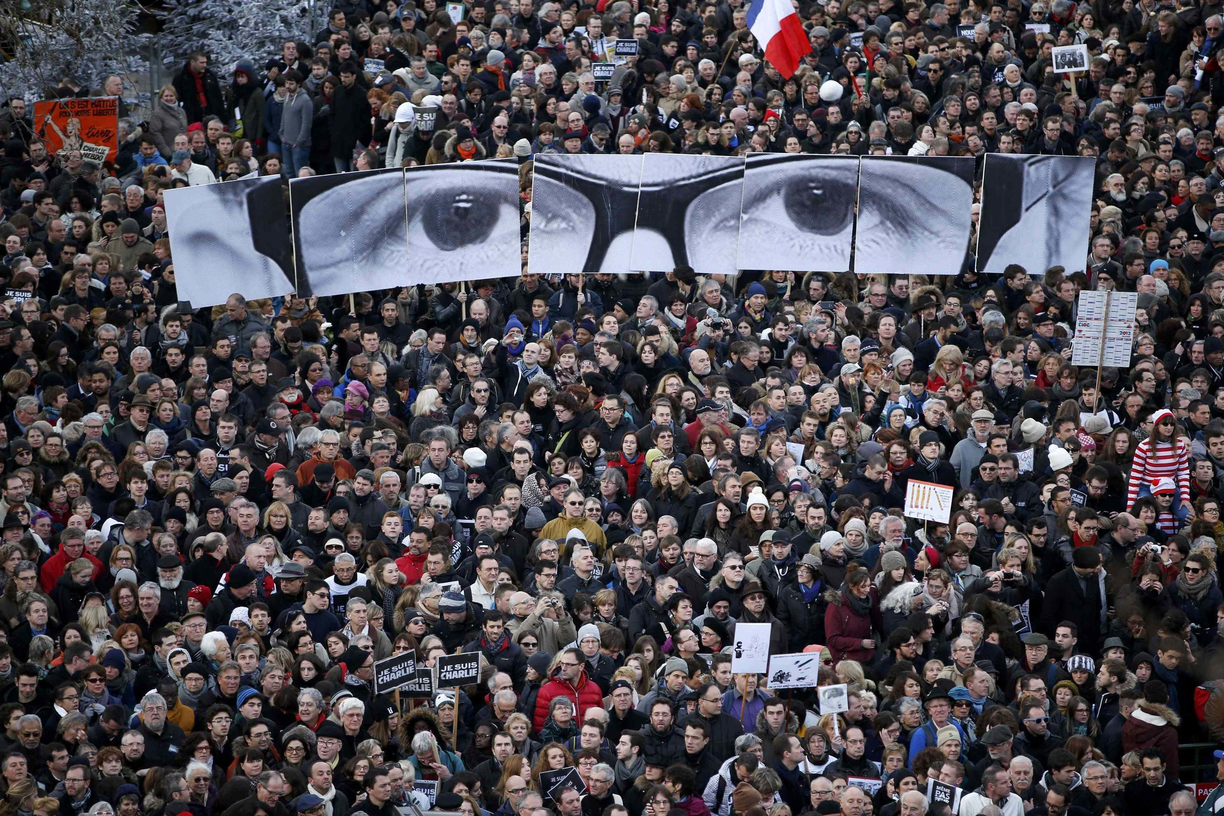 """People hold panels to create the eyes of late Charlie Hebdo editor  """"Charb"""", as millions of French citizens take part in a solidarity march in the streets of Paris, 11 January 2015."""