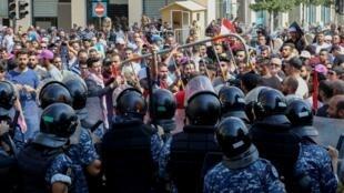La police anti-émeute a repoussé les manifestants qui tentaient de franchir les barrières de sécurité devant le siège du gouvernement Place des Martyrs, à Beyrouth, le 29 septembre 2019.