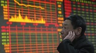 Một người chơi chứng khoán cao niên trầm ngâm trước bảng chỉ số cổ phiếu đang đi xuống.