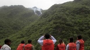 Rescue teams look at the crash site near Islamabad.