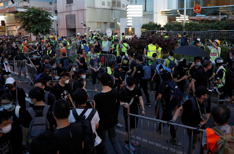 Người biểu tình tháo gỡ các hàng rào bên ngoài Văn phòng liên lạc Trung Quốc, sau khi tuần hành kêu gọi cải cách dân chủ ở Hồng Kông ngày 21/07/2019.