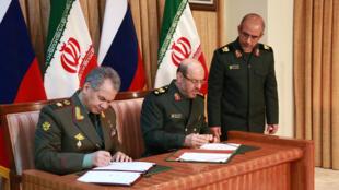 Le ministre russe de la Défense Sergueï Choïgou (g) et son homologue iranien Hossein Dehghan, lors de la signature d'un protocole d'accord pour renforcer leur coopération militaire, à Téhéran, le 20 janvier 2015.