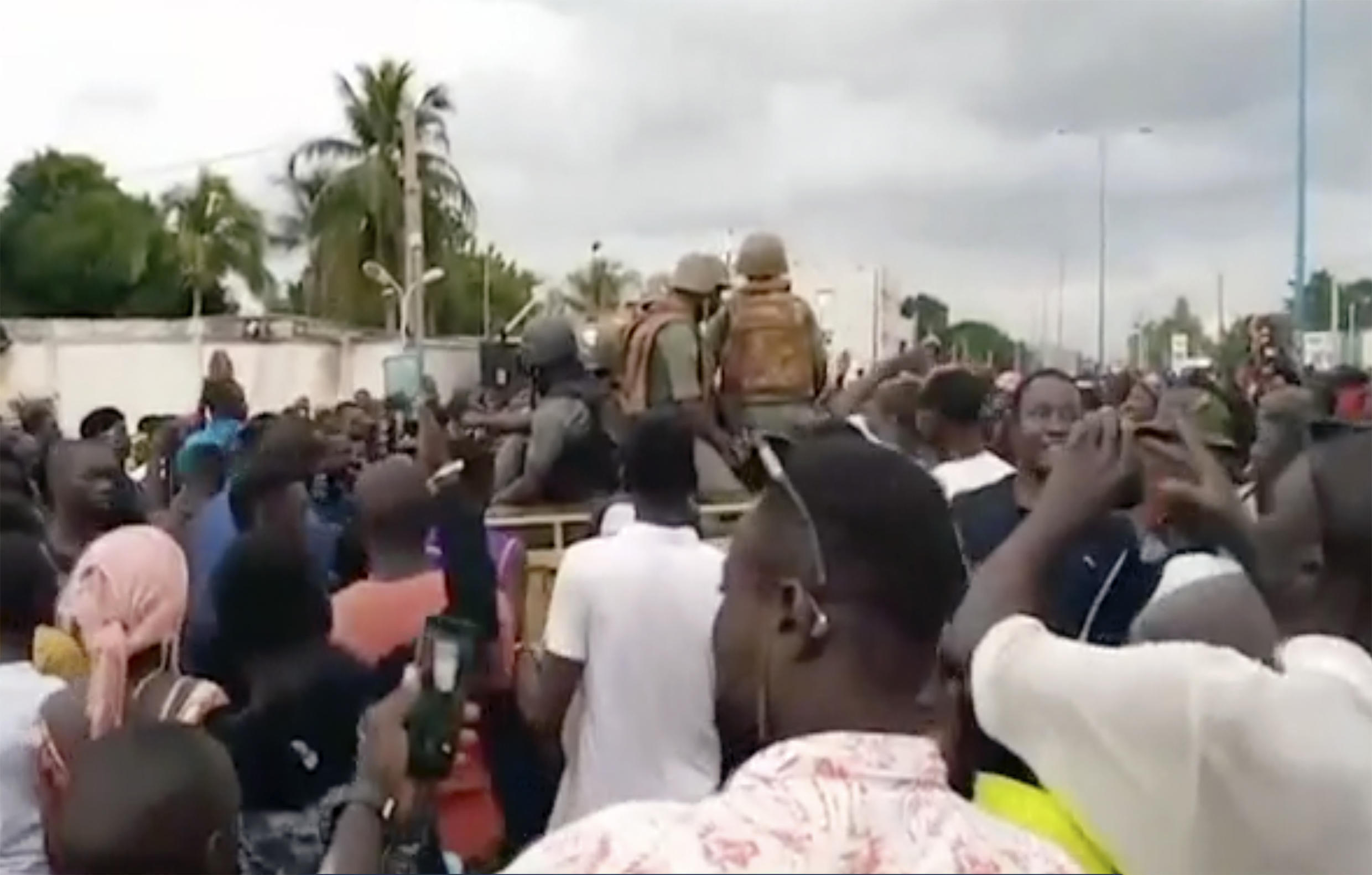 Soldiers are greeted by crowds of people, as military are stationed around President Ibrahim Boubacar Keita's city residence where he and the prime minister were later detained, in Bamako, Tuesday Aug. 18, 2020.  Malian President Ibrahim Boubacar Keita appeared on state television to announce his resignation with immediate effect late Tuesday.
