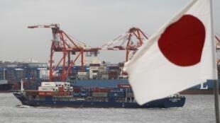 Bandeira japonesa diante de cargueiro ancorado no porto de Tóquio; a crise diplomática ameaça o comércio entre China e Japão.