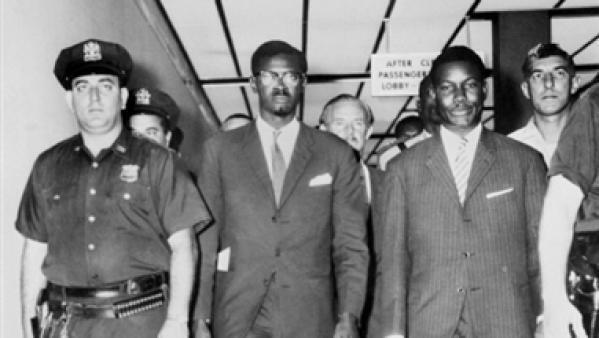 Patrice Lumumba, président du Conseil de la République du Congo, quitte l'aéroport d'Idlewild à New York le 24 juillet 1960, escorté par des policiers américains. L'indépendance du Congo a été proclamée le 30 juin 1960.