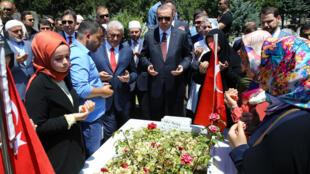 O presidente Recep Tayyip Erdogan e o primeiro-ministro Binali Yildirim rezam diante do túmulo de vítimas do golpe militar frustrado de 15 julho de 2016.