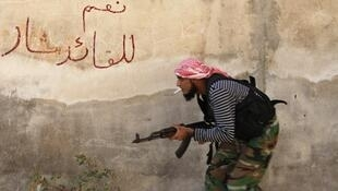 Un combattant de l'Armée syrienne libre, à Alep. Sur le mur, on peut lire «oui au leader Bachar».