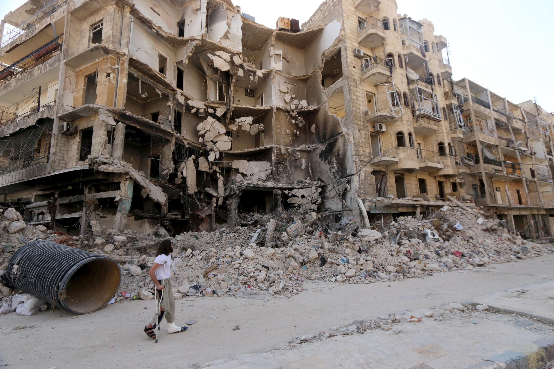 Homem caminha em frente a ruínas na cidade velha de Aleppo, em foto tirada no dia 27 de junho de 2015.