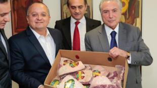 Pedro Taques, governador do estado de Mato Grosso e o presidente Michel Temer mostram exemplares de carne bovina produzida no Brasil.