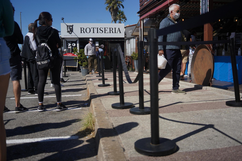 Des Uruguayens gardent leurs distances dans la queue d'un magasin à Montevideo le 10 avril 2020.