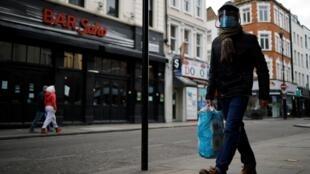 Un viandante con mascarilla y visera camina por una semidesierta Old Compton Street, en el céntrico barrio del Soho, el 15 de enero de 2021 en Londres
