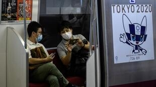 Train passengers in Tokyo wear masks near a poster for the 2020 Olympics. The development of a vaccine will be key to allowing the delayed Games to proceed in a year's time, the organising committee president said Wednesday