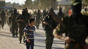 Un jeune Palestinien observe des membres du Hamas dans le centre de la bande de Gaza, le 20 septembre 2013.