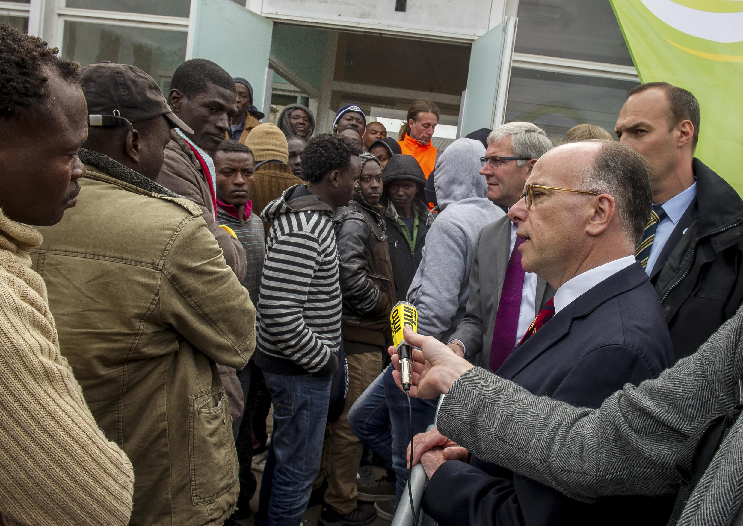 4 May 2015 - French Interior Bernard Cazeneuve speaks with migrants as he visits the 'Day centre Jules Ferry', a shelter for migrants in the 'New Jungle'