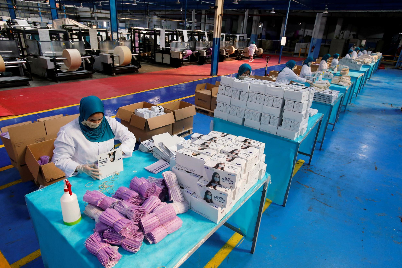 Des employés emballent des masques protecteurs contre le Covid-19 dans une usine à Casablanca, le 10 avril 2020, alors que le Maroc augmente sa production.