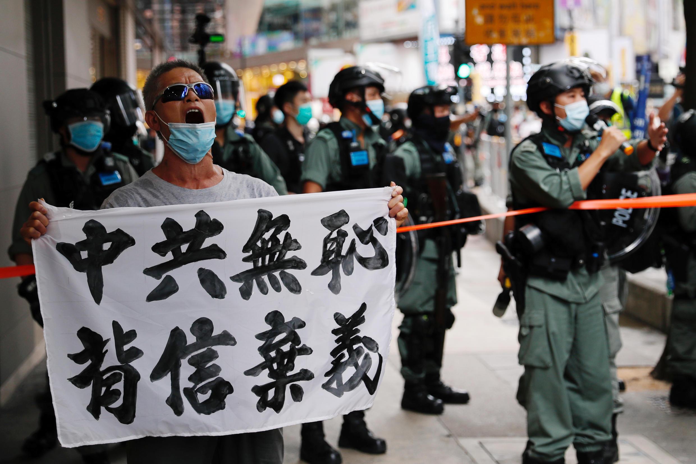 """2020年7月1日,一名香港人高举""""中共无耻背信弃义""""巨幅标语抗议北京强加港版国安法。"""