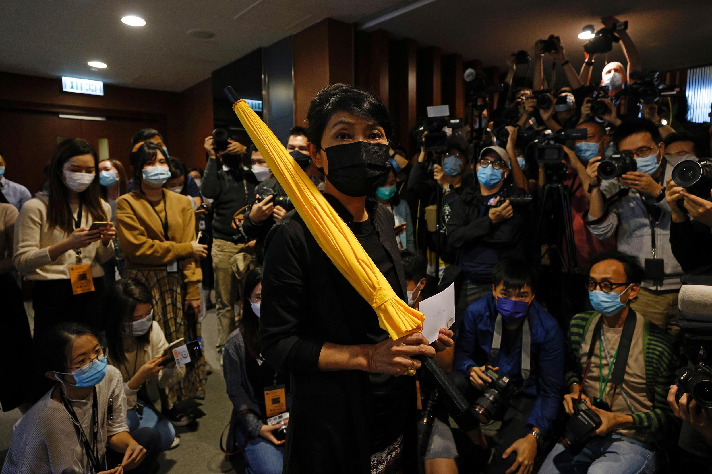 Nghị sĩ ủng hộ dân chủ Claudia Mo tay cầm dù vàng, biểu tượng của phong trào đấu tranh Occupy Central, tay cầm lá thư từ nhiệm. Hồng Kông, Trung Quốc, ngày 12/11/2020.