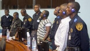 De gauche à droite les trois condamnés sierra-léonais entourés de policiers lors de leur procès : Augustine Gbao, Maurice Kallon, Issa Hassan Sesay.