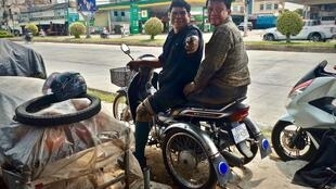 Hin Bunthen, à droite, adapte des motos afin que des personnes souffrant d'un handicap moteur puissent les conduire.